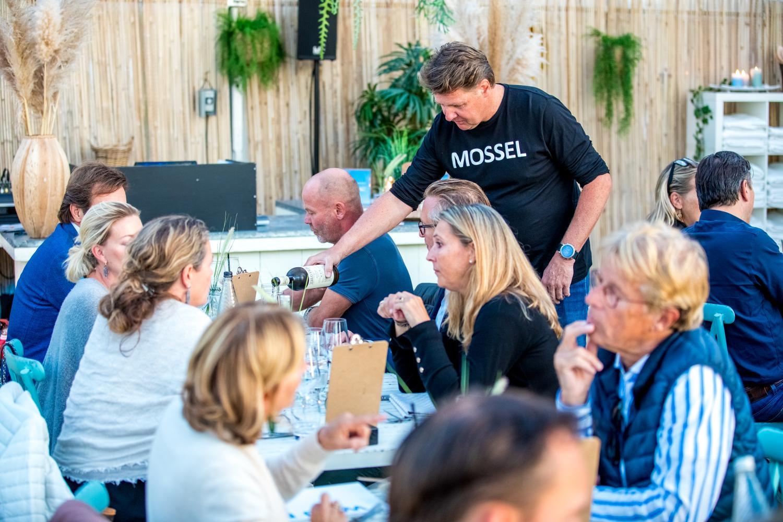 10. Mosseldiner 2019_Maarten schenkt wijn in aan tafel